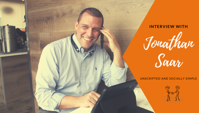 Interview with Jonathan Saar - Unscripted and Socially Simple-Jonathan on his phone smiling.